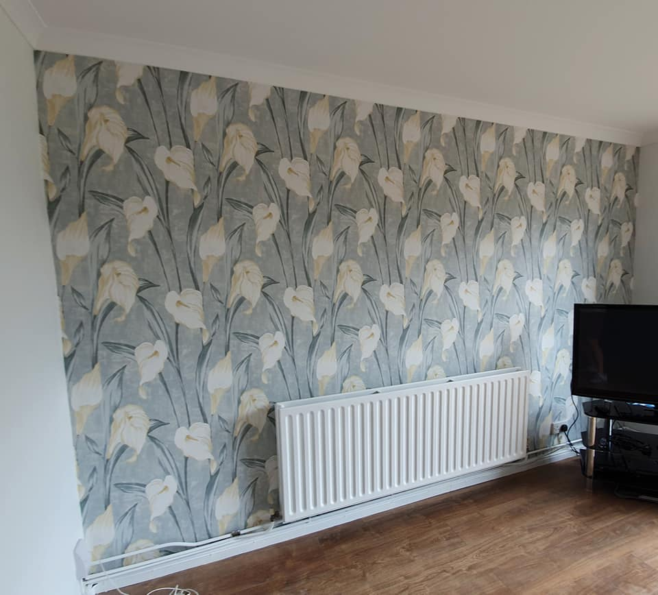 A bright floral wallpapered and painted lounge