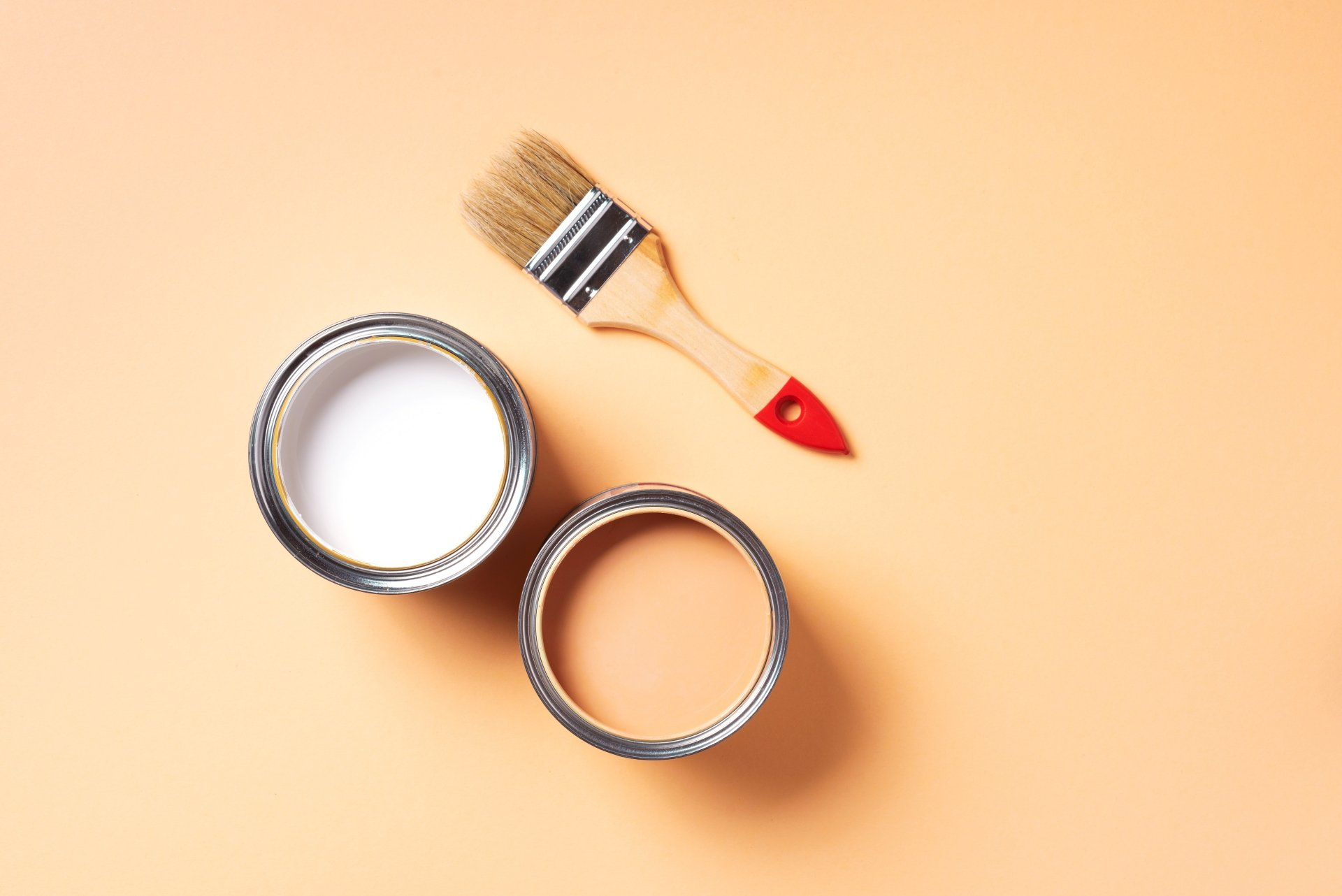 Paint brush and open paint can with on pastel background.