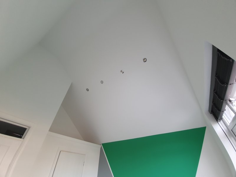 A tall ceiling and an eye catching geometric design in bedroom