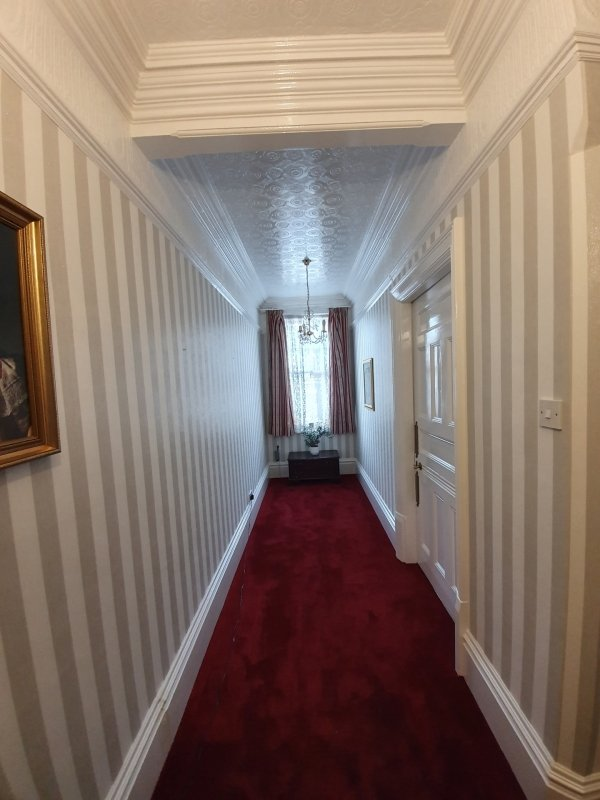 A traditional landing with striped wallpaper and bold red carpet