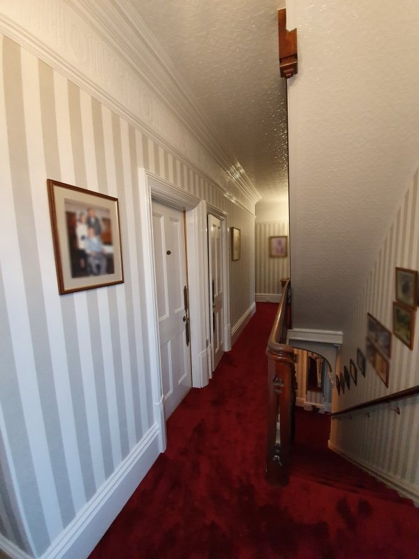 A traditional landing and stairs with striped wallpaper and bold red carpet