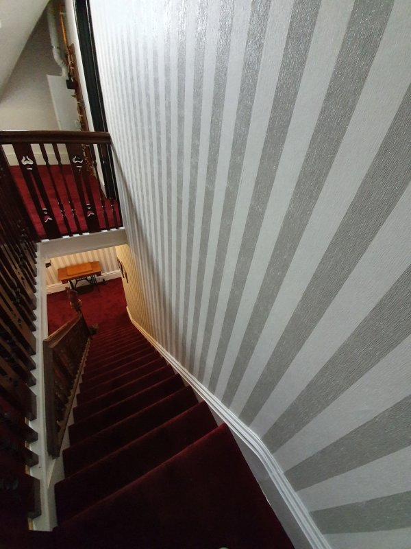 A traditional stairwell with striped wallpaper and bold red carpet