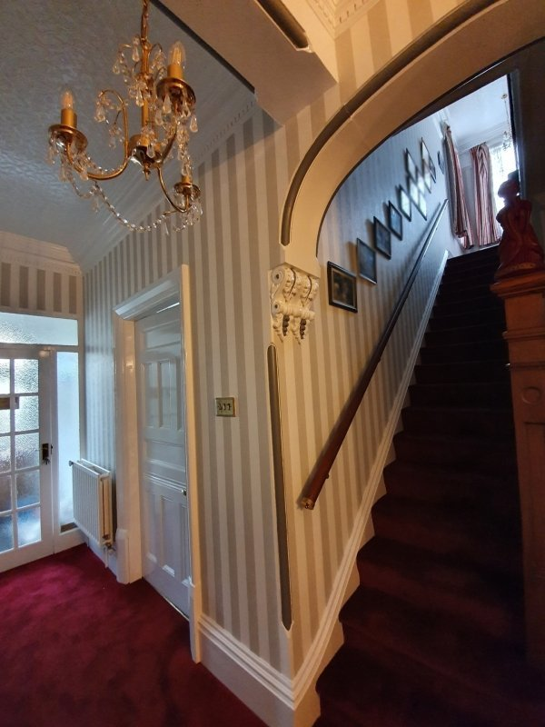 A traditional hallway and stairs with striped wallpaper and bold red carpet