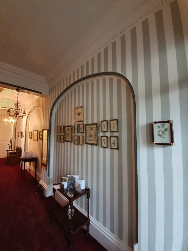 A traditional hallway with striped wallpaper and bold red carpet