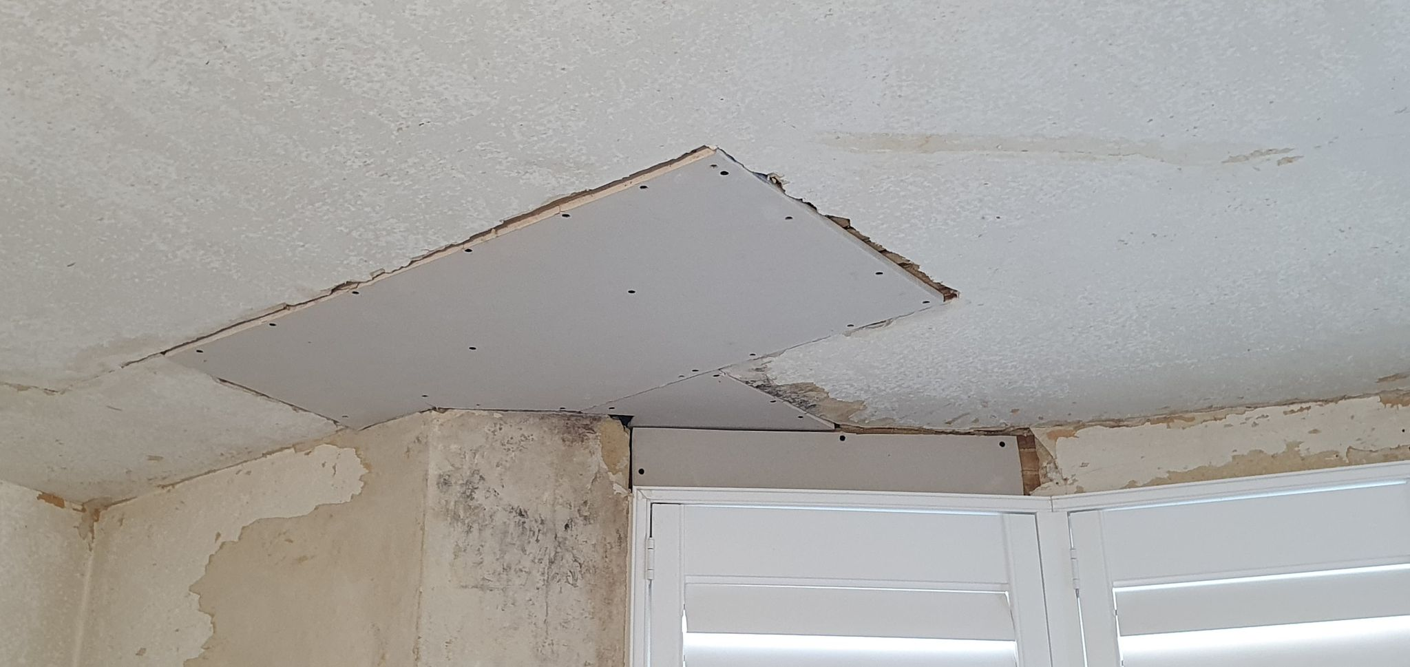 Plasterboard cut to fit damaged ceiling