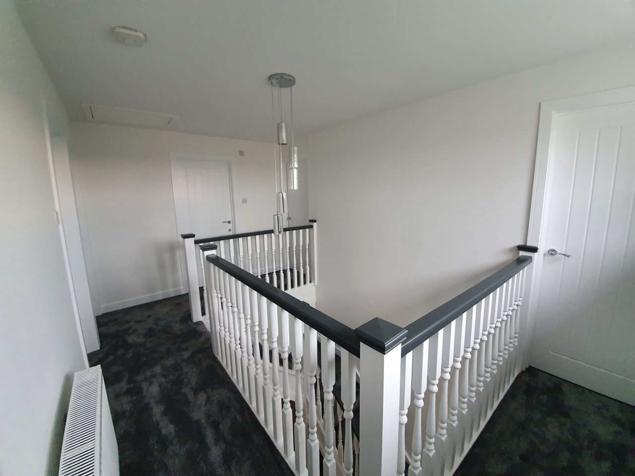 A hallway, stairwell and landing after being decorated, striking black and white