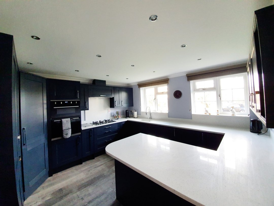 Midnight blue kitchen with blue grey walls and white ceiling